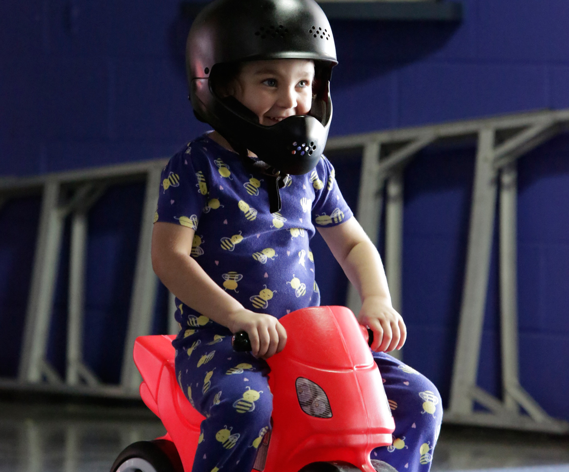Child on toy motorcycle with helmet