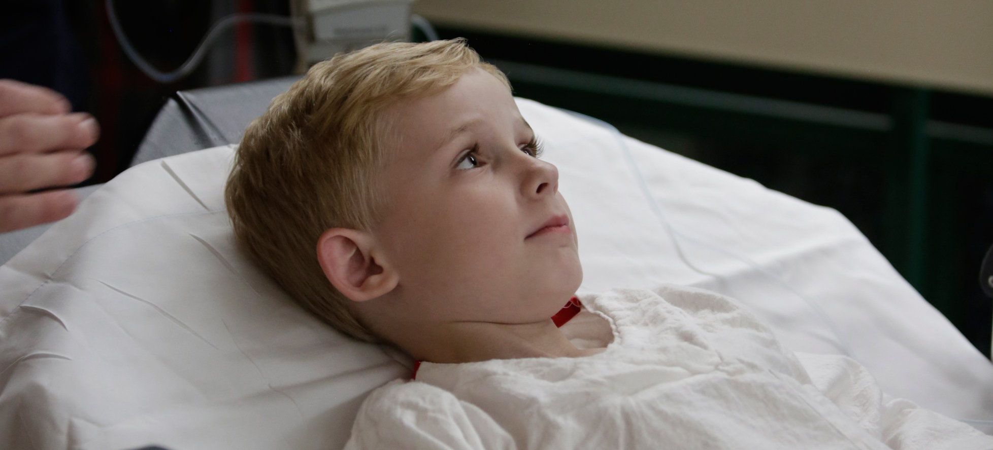 boy lying in hospital bed