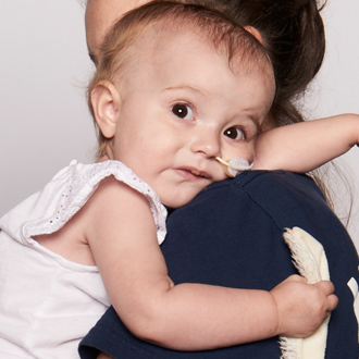 SickKids patient resting on mother's shoulder