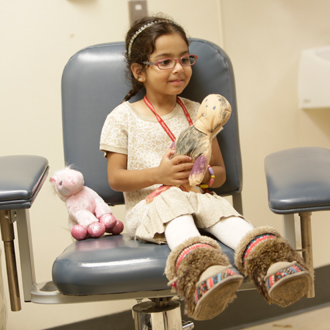SickKids patient in hospital room holding doll