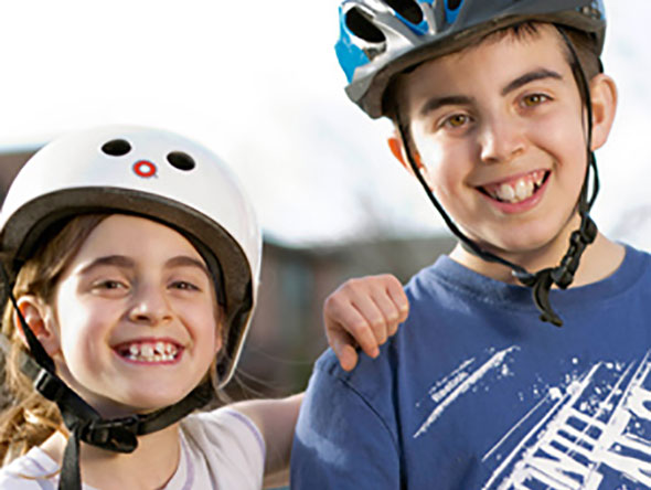 Two kids wearing bicycle helmets