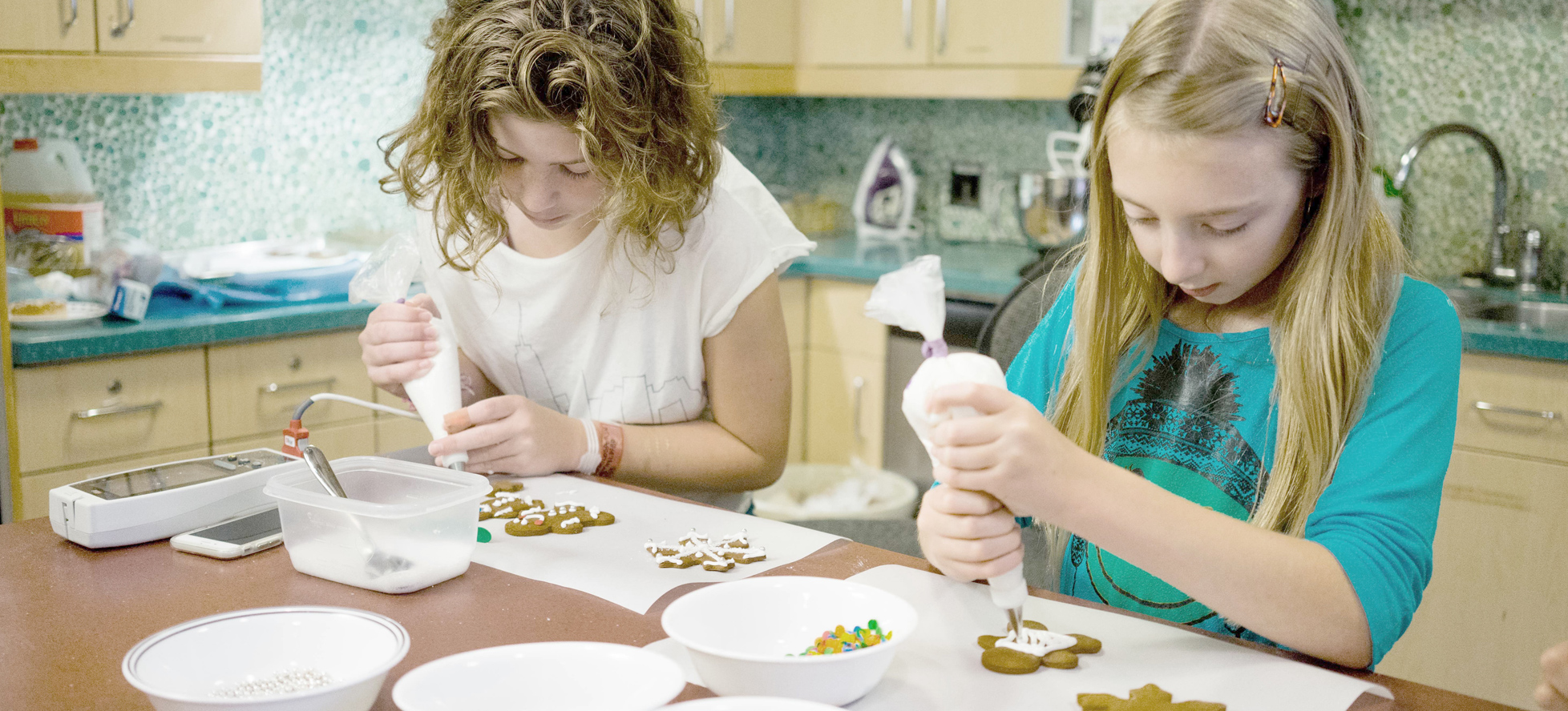 two girls decorating cookies