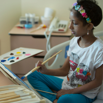 Girl painting on hospital bed