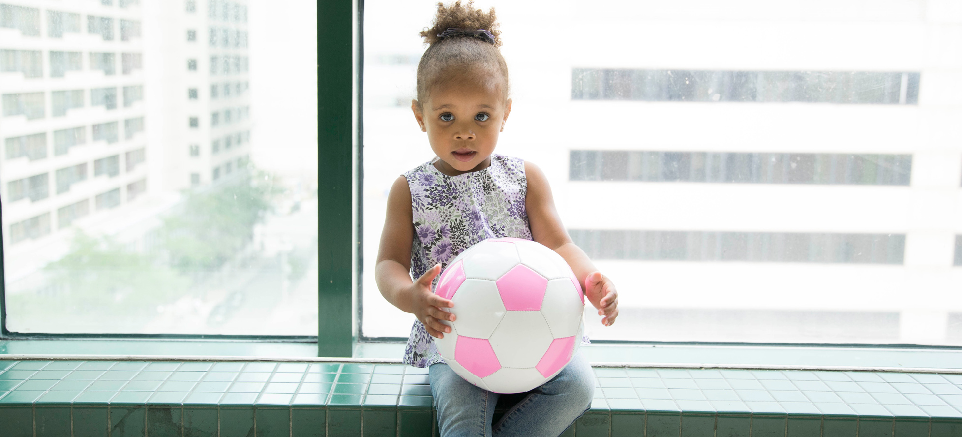 Girl sitting by window with pink soccer ball