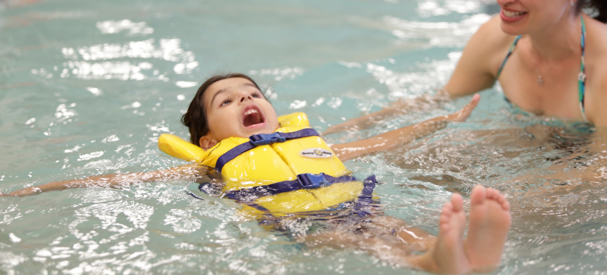 Little girl doing a backfloat in a pool with life jacket on