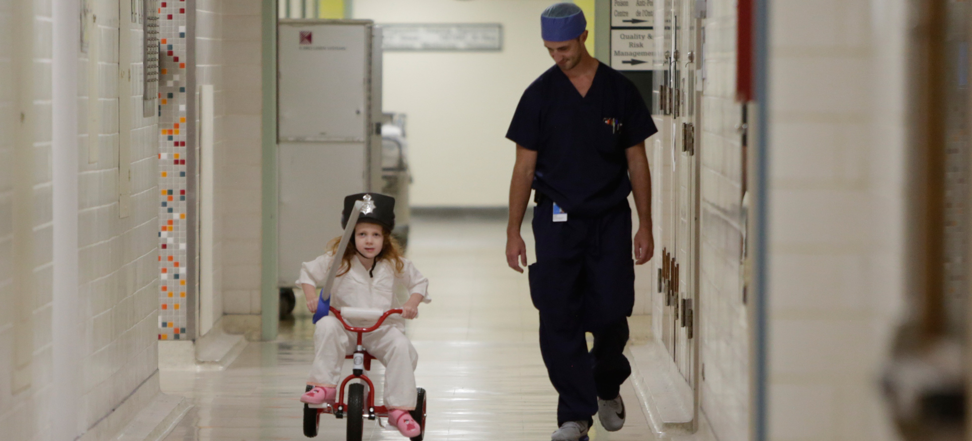 girl riding tricycle down hospital hallway
