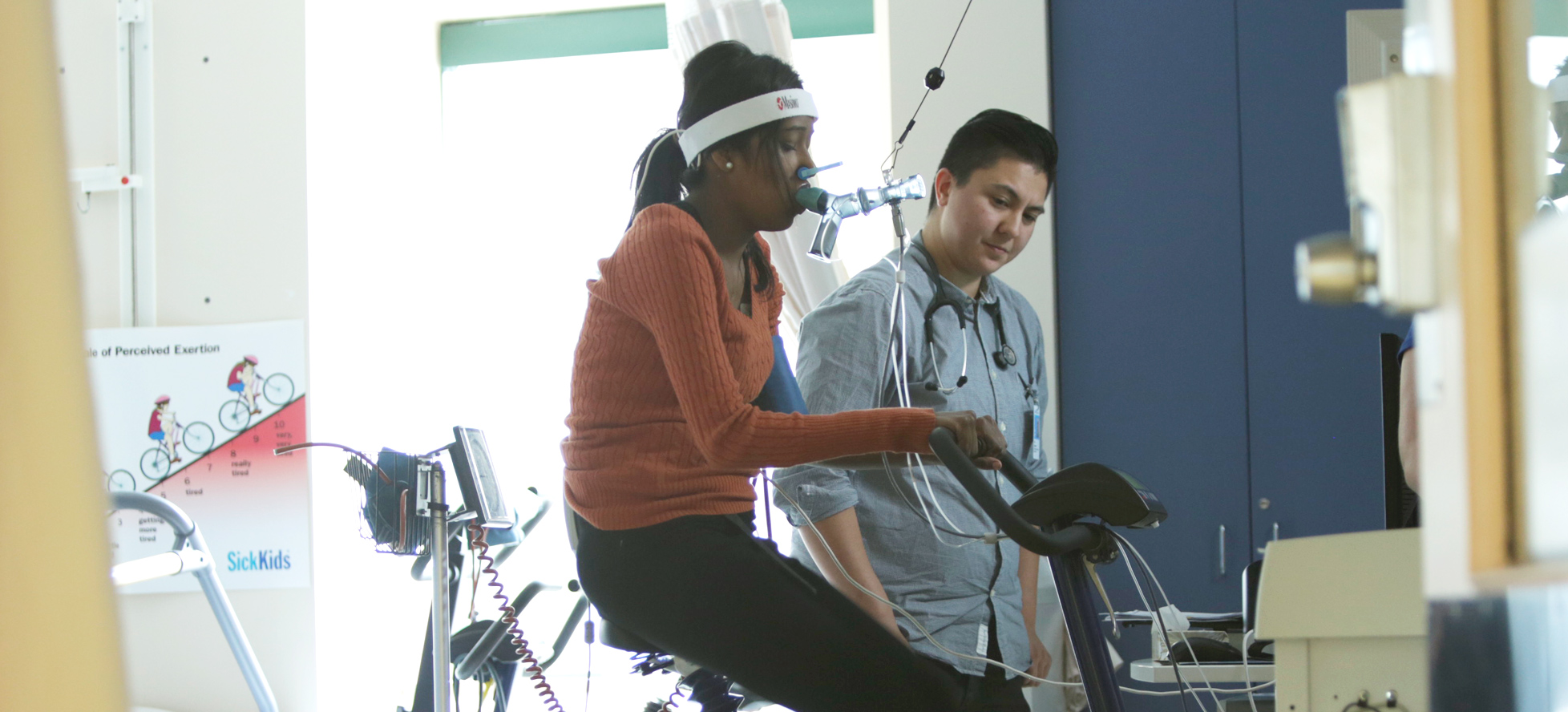 female teenage patient with breathing apparatus on stationary bike