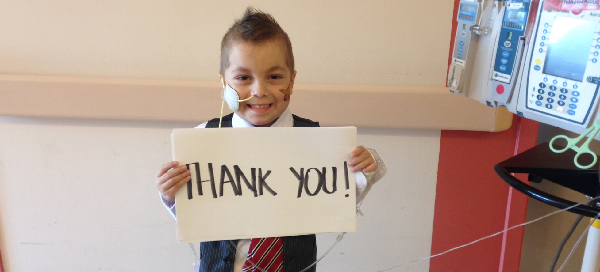 Little boy with IV pole holding up thank you sign