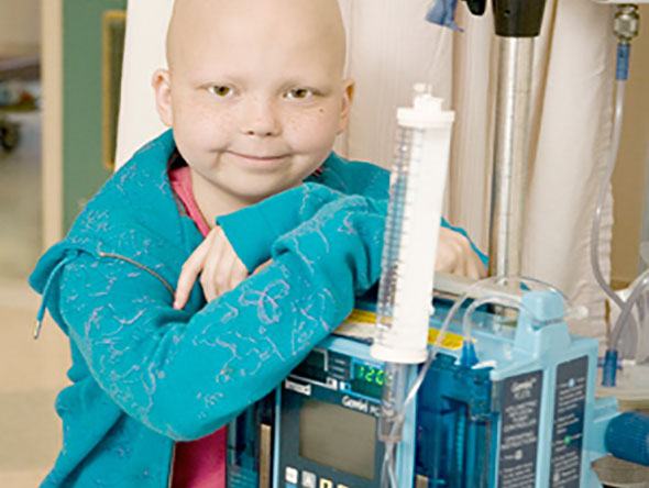 Bald girl leaning on IV pole