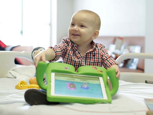 Little boy in plaid shirt with toy on hospital bed