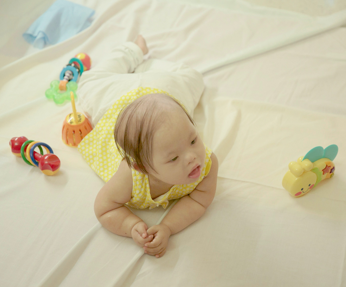 Baby in yellow dress lying on belly with toys