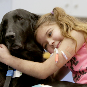 SickKids patient hugging dog