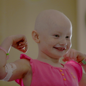 Bald SickKids patient showing arm muscles