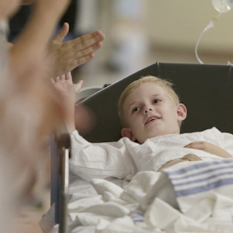 SickKids patient in bed giving high five